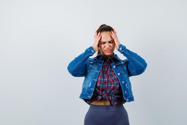 Młoda kobieta w kraciastej koszuli, kurtce, spodniach z rękami na głowie i patrząc na zmęczoną, widok z przodu.