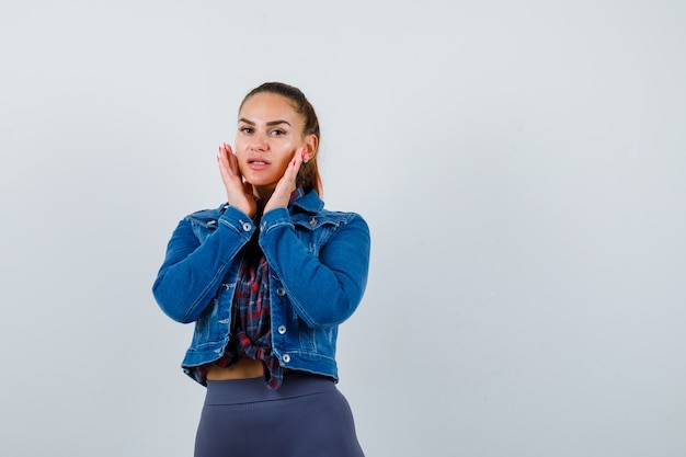 Młoda kobieta w kraciastej koszuli, kurtce, spodniach z rękami na policzkach i patrząc ładny, widok z przodu.