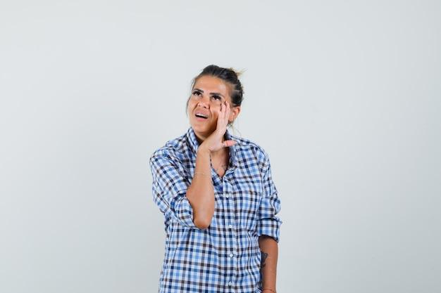 Młoda kobieta w kraciastej koszuli mówi coś potajemnie i wygląda na skupioną.