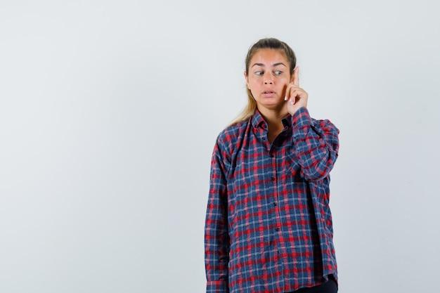 Młoda kobieta w kraciastej koszuli podnosząc palec wskazujący w geście eureki i patrząc zamyślony
