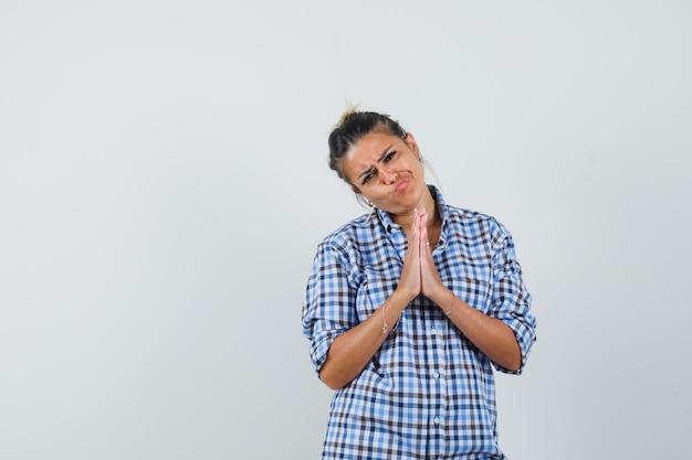 Młoda kobieta w kraciastej koszuli pokazując gest modlitwy i patrząc bezradnie.