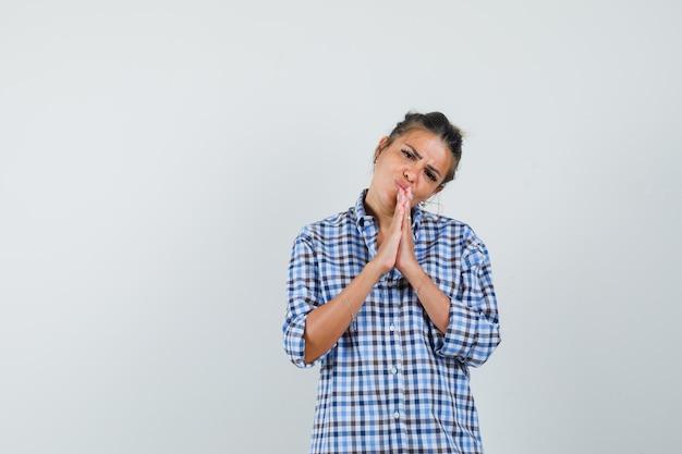 Młoda kobieta w kraciastej koszuli pokazując gest modlitwy i patrząc z nadzieją.
