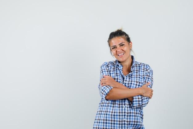 Młoda kobieta w kraciastej koszuli przytulanie siebie i wyglądająca uroczo.