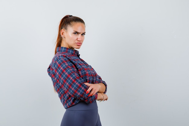Młoda kobieta w kraciastej koszuli, spodniach stojących ze skrzyżowanymi rękami i wyglądających pewnie, widok z przodu.