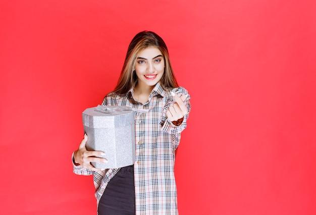 Młoda kobieta w kraciastej koszuli trzyma srebrne pudełko i dzwoni do odbiorcy, żeby je wziął