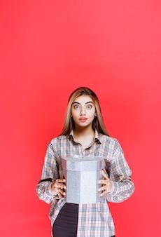 Młoda kobieta w kraciastej koszuli trzyma srebrne pudełko upominkowe