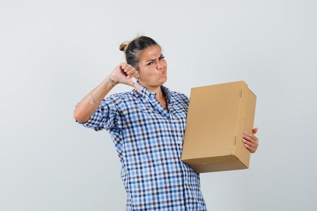 Młoda kobieta w kraciastej koszuli, trzymając pudełko, pokazując kciuk w dół i patrząc niezadowolony.