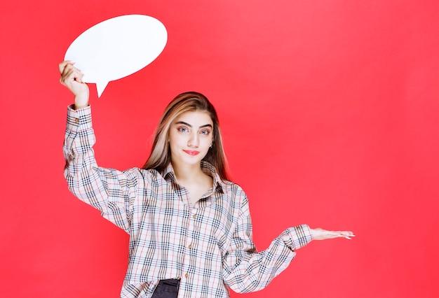 Młoda kobieta w kraciastej koszuli trzymająca owalną tablicę informacyjną