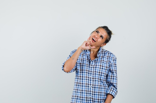 Młoda kobieta w kraciastej koszuli tworząc nowy pomysł i patrząc zamyślony.
