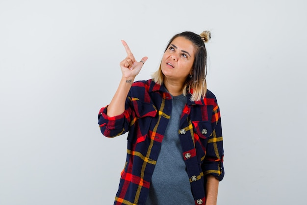 Młoda kobieta w kraciastej koszuli, wskazując na lewy górny róg i wyglądająca na pewną siebie