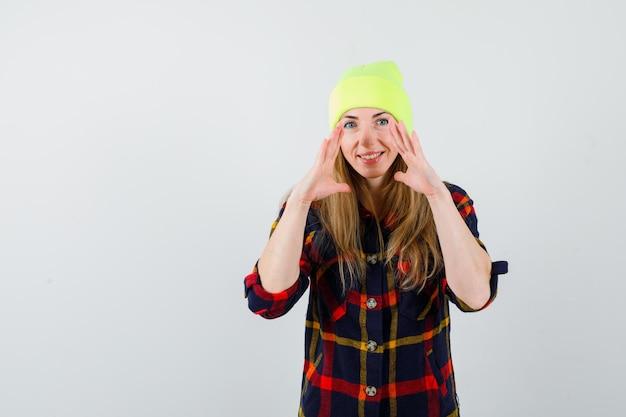 Młoda kobieta w kraciastej koszuli z kapeluszem