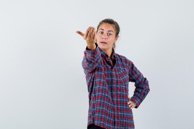 Młoda kobieta w kraciastej koszuli zaprasza do przyjścia, trzymając rękę w pasie i wyglądając pewnie