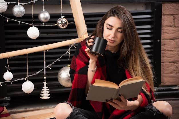 Młoda kobieta w kratkę w kratę siedzi na podłodze i czyta książkę.