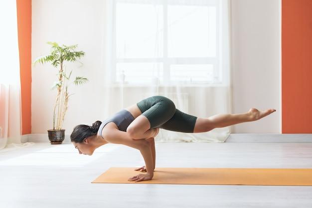Młoda kobieta w krótkich legginsach i podkoszulku ćwicząca jogę wykonuje w studio na macie ćwiczenie eka pada golovasana poza mędrca