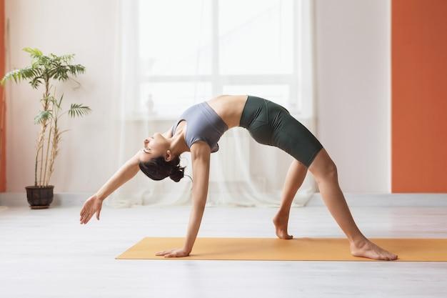 Młoda kobieta w krótkich legginsach i podkoszulku wykonuje jogę w pokoju stojąc na macie ćwiczenie kamatkarasana taniec poza psem
