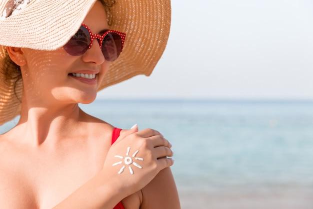 Młoda kobieta w kształcie słońca na dłoni z kremu przeciwsłonecznego na plaży.