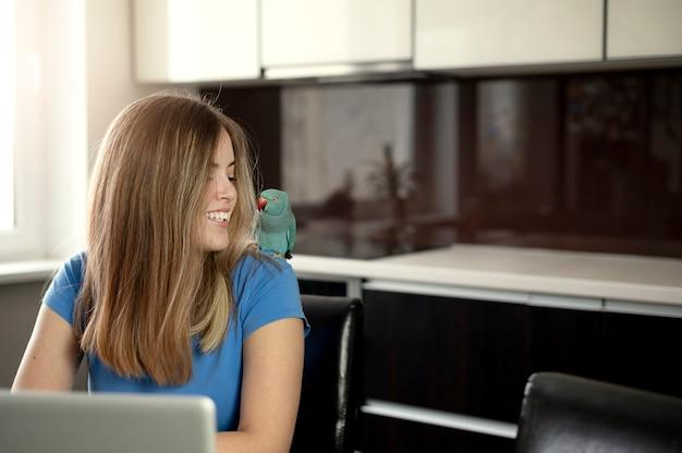 Młoda kobieta w kuchni podczas kwarantanny. samodzielnie i rozmawiaj przez telefon.