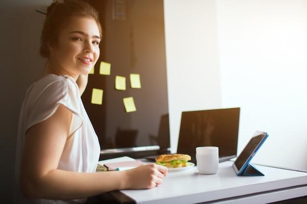 Młoda kobieta w kuchni. rozochocony szczęśliwy girlworking od domu. trzymaj żółte naklejki z zadaniami na lodówce.
