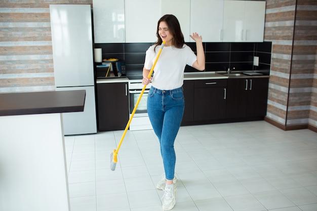 Młoda kobieta w kuchni. trzymanie mopa lub miotły w dłoni i śpiewanie na głos. używanie sprzętu czyszczącego jako mikrofonu. po myciu podłogi.