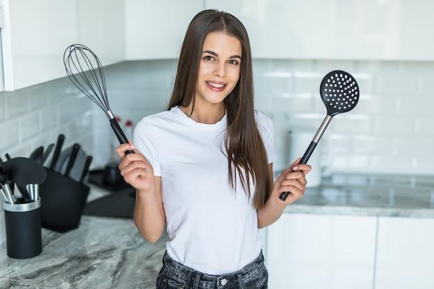 Młoda kobieta w kuchni. w rękach trzyma narzędzia do gotowania żywności.