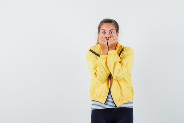 Młoda kobieta w kurtce, koszulce gryzie pięści emocjonalnie i wygląda na przestraszoną, widok z przodu.