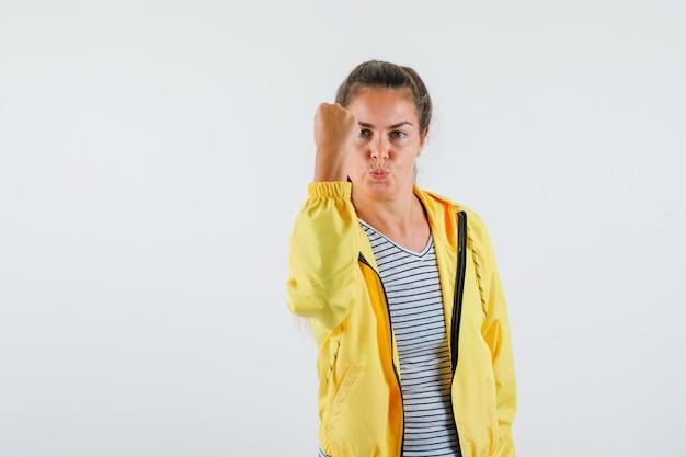 Młoda kobieta w kurtce, koszulce pokazuje zaciśniętą pięść i wygląda pewnie, widok z przodu.