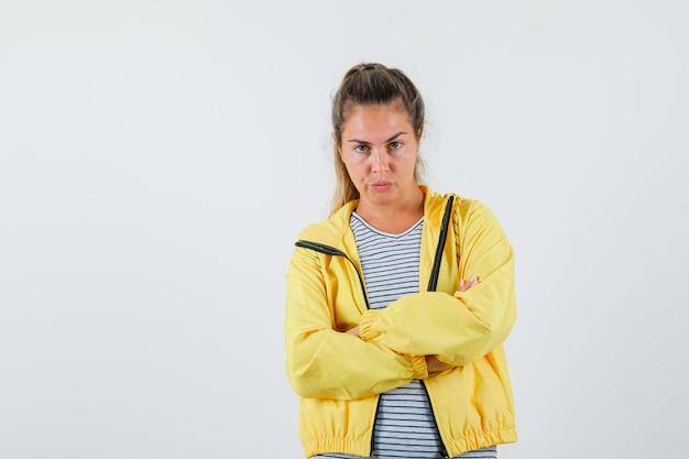 Młoda kobieta w kurtce, koszulce stojącej ze skrzyżowanymi rękami i patrząc poważnie, widok z przodu.