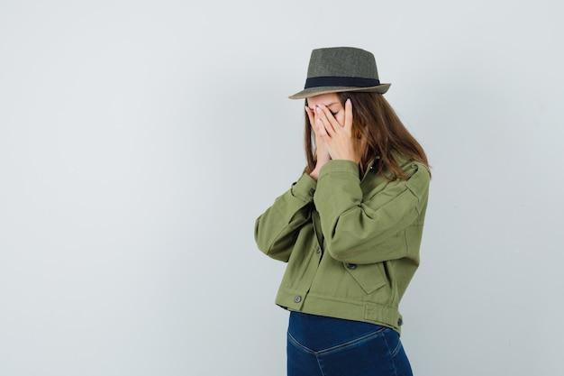 Młoda kobieta w kurtce, spodniach, kapeluszu, trzymając się za ręce na twarzy i wyglądająca na wyczerpaną, widok z przodu.