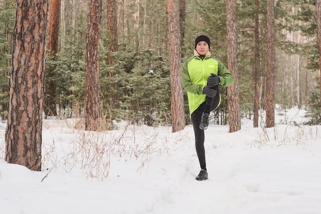 Młoda kobieta w kurtce, trzymając nogę w pobliżu brzucha, rozciągając ją na treningu w zimowym lesie
