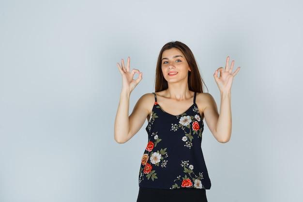 Młoda kobieta w kwiatowy top pokazano ok gest i wyglądam uroczo