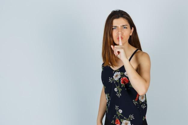 Młoda kobieta w kwiecistej górze pokazując gest ciszy i patrząc ponuro