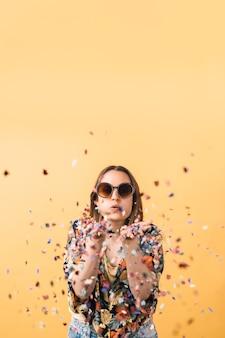 Młoda kobieta w kwiecistej koszuli i dużych okrągłych okularach przeciwsłonecznych dmuchająca konfetti