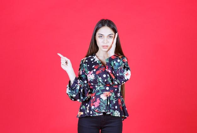 Młoda kobieta w kwiecistej koszuli stojąca na czerwonej ścianie i pokazująca lewą stronę