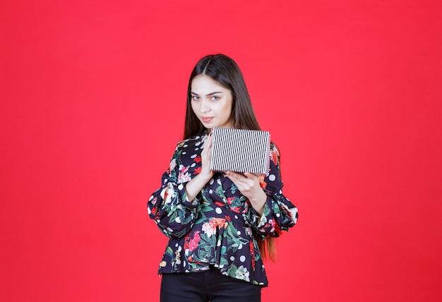 Młoda kobieta w kwiecistej koszuli trzyma srebrne pudełko i wygląda na zamyśloną