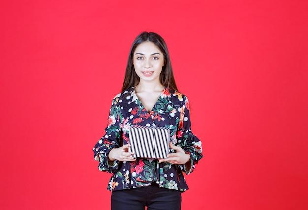 Młoda kobieta w kwiecistej koszuli trzyma srebrne pudełko upominkowe
