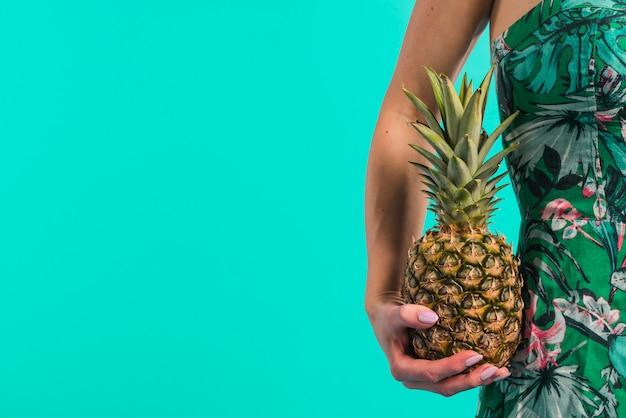 Młoda kobieta w kwiecistej sukni trzyma ananasa