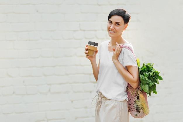 Młoda kobieta w lekkich letnich ubraniach z eko torbą warzyw, zieleni i kubkiem kawy wielokrotnego użytku. zrównoważony styl życia. koncepcja przyjazna dla środowiska.