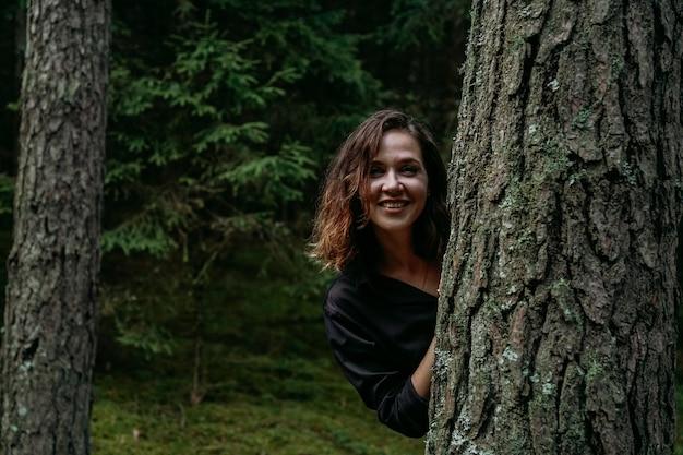 Młoda kobieta w lesie iglastym wygląda zza drzewa. szczęśliwa młoda kobieta patrząca w kamerę i uśmiechnięta