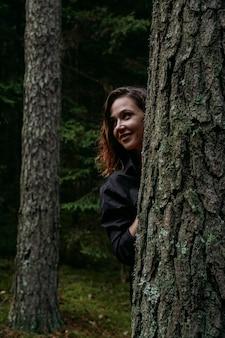 Młoda kobieta w lesie iglastym wygląda zza drzewa. szczęśliwa młoda kobieta