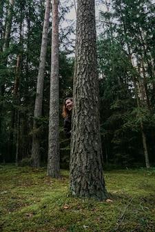 Młoda Kobieta W Lesie Iglastym Wygląda Zza Drzewa Premium Zdjęcia