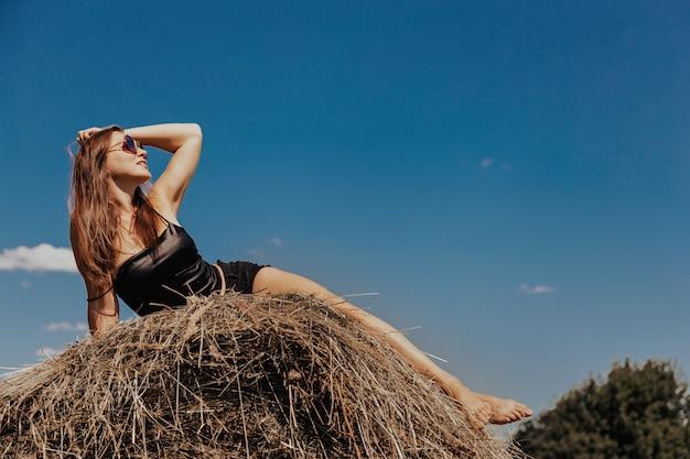 Młoda kobieta w letni dzień na polu stogu siana