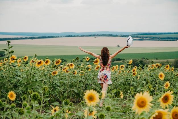 Młoda kobieta w letniej sukience biegnie po polu ze słonecznikami rozłożonymi na boki.