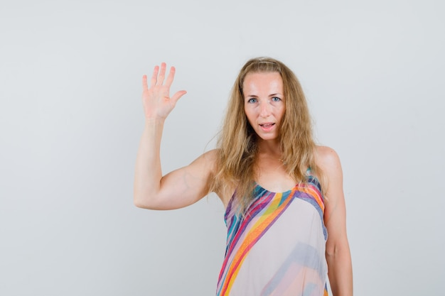 Młoda kobieta w letniej sukience macha ręką, aby się pożegnać lub przywitać i wyglądać rozsądnie