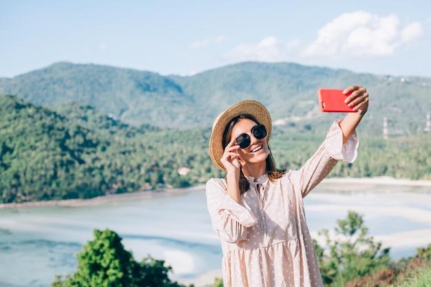 Młoda kobieta w letniej sukience, słomkowym kapeluszu i okularach przeciwsłonecznych robi wideokonferencję z jej smartfonem