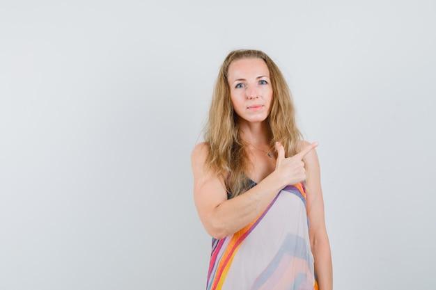 Młoda kobieta w letniej sukience, wskazując na bok ze znakiem broni i patrząc pewnie