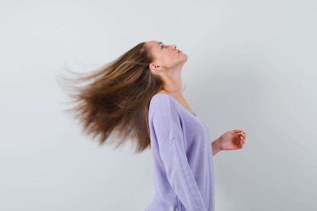 Młoda kobieta w liliowej bluzce macha włosami i wygląda imponująco.