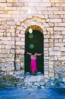 Młoda kobieta w liliowej spódnicy stoi plecami na ruinach starożytnej fortecy