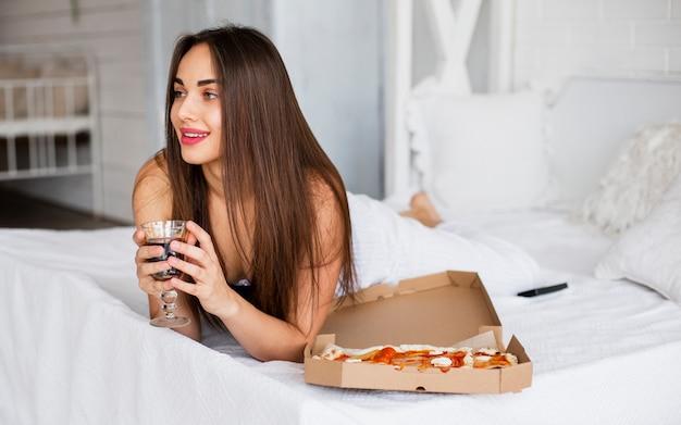 Młoda kobieta w łóżku jedzenie pizzy