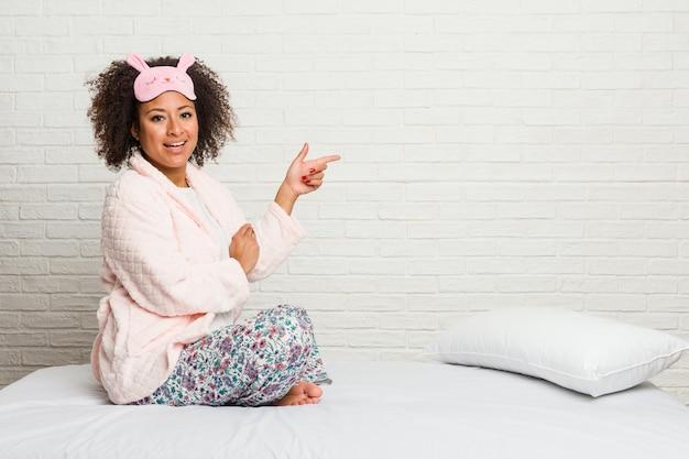 Młoda kobieta w łóżku nosząca pijama uśmiecha się wesoło wskazując palcem wskazującym daleko.