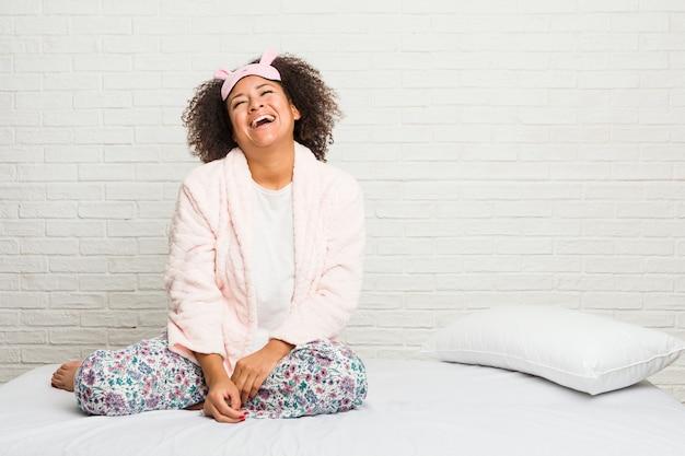 Młoda kobieta w łóżku ubrana w pijama zrelaksowana i szczęśliwa ze śmiechu, z wyciągniętą szyją pokazującą zęby